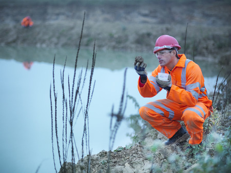 reflective: Worker examining plants in quarry LANG_EVOIMAGES