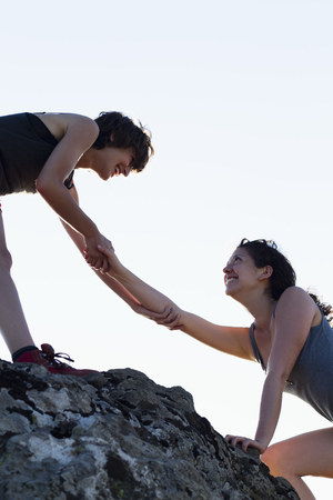reaches: Hikers helping each other climb rock LANG_EVOIMAGES