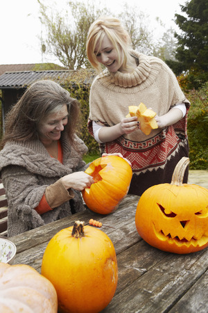 waist down: Mother and daughter carving pumpkins