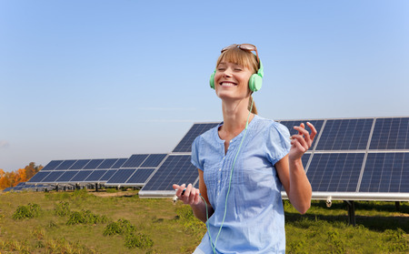 musically: Woman with headphones and solar panels LANG_EVOIMAGES