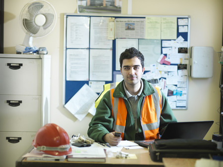 prideful: Construction worker sitting in office