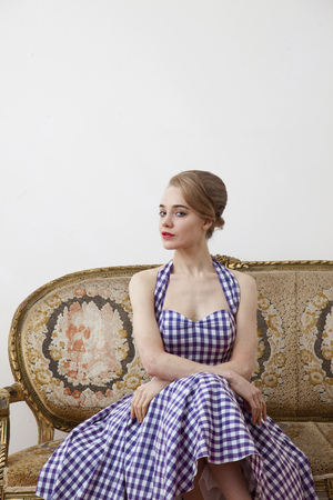 poised: Woman sitting on ornate couch