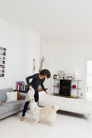 omnivore: Woman playing with dog in living room