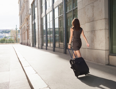 shadowed: Businesswoman rolling luggage outdoors LANG_EVOIMAGES