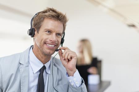 handsfree telephones: Businessman wearing headset at desk