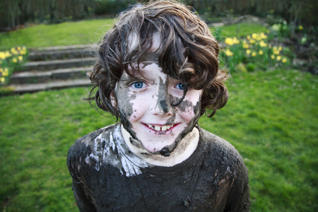 Boy's smiling face covered in mud
