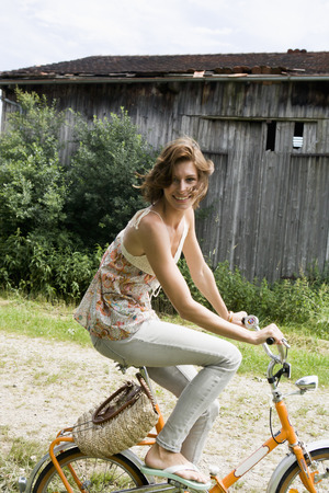Woman riding bicycle on rural road LANG_EVOIMAGES