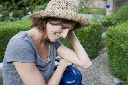 held down: Smiling woman holding watering can