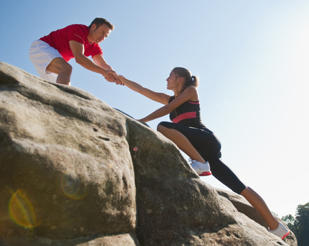 Rock climbers helping each other LANG_EVOIMAGES