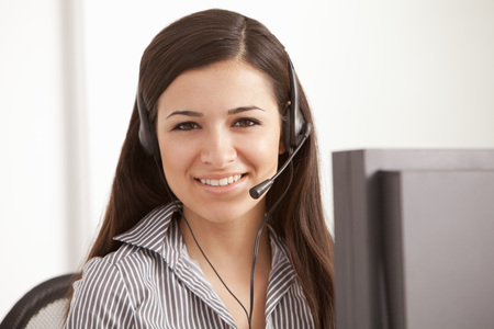 handsfree telephones: Businesswoman talking on headset at desk