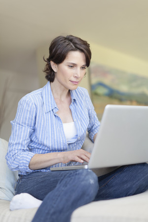 telecommuter: Smiling woman using laptop on couch