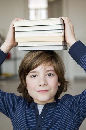 Boy balancing books on his head
