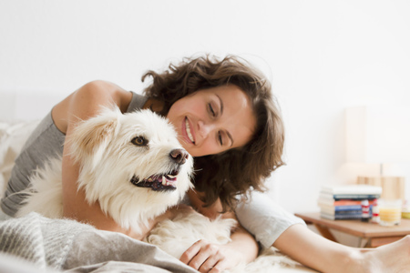 Smiling woman petting dog in bed LANG_EVOIMAGES