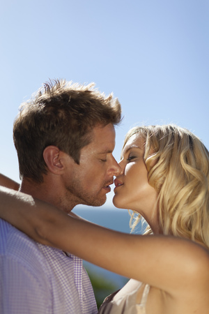 smooch: Smiling couple kissing outdoors