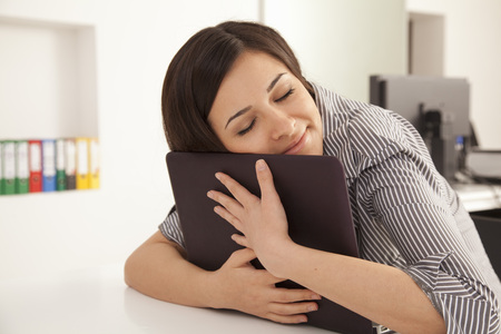 Businesswoman hugging computer in office
