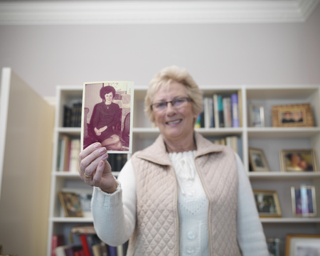 preceded: Older woman holding old photograph