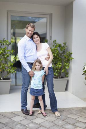 Family smiling outside front door LANG_EVOIMAGES