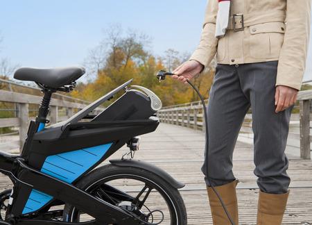 Woman charging electric bike outdoors