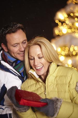 Man giving girlfriend present outdoors