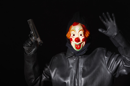 yielding: Man in clown mask holding gun