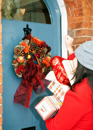 abodes: Woman with wrapped gifts at front door