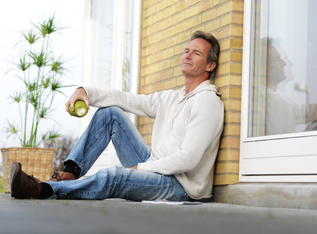 mans watch: Man eating apple on porch LANG_EVOIMAGES