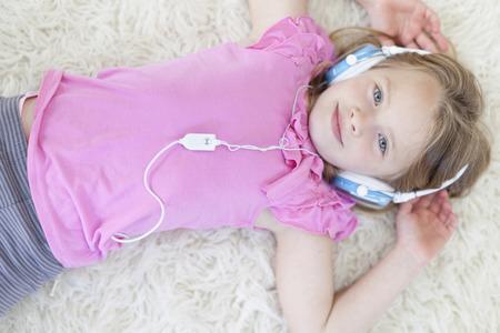 Girl listening to headphones on carpet