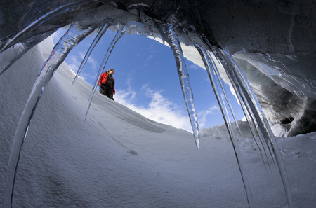 snows: Hiker viewed from glacial cave
