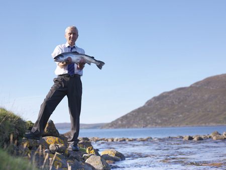 Businessman with salmon by lake