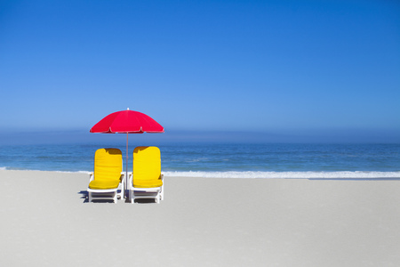 Empty Lawn Chairs And Umbrella On Beach