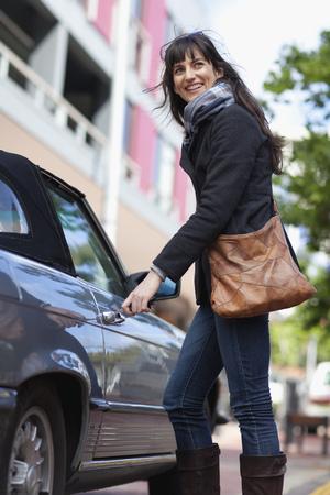 Woman unlocking car on city street