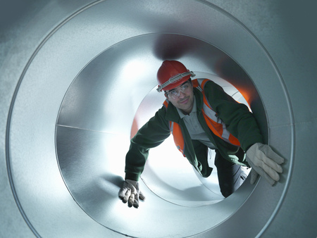 Worker climbing in steel piping
