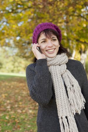 reconocimientos: Mujer hablando por teléfono celular en el parque LANG_EVOIMAGES