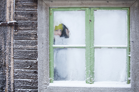 remoteness: Woman peering out frosty window