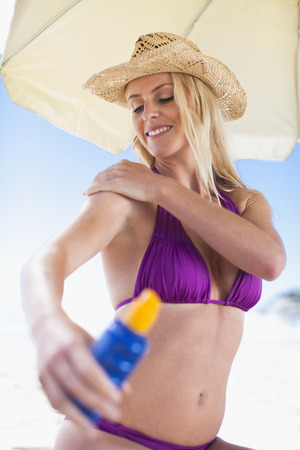 Woman applying sunscreen on beach LANG_EVOIMAGES