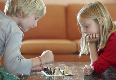 resolving: Children playing chess in living room LANG_EVOIMAGES