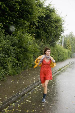 Smiling woman running in rain LANG_EVOIMAGES