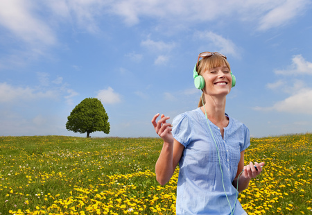 Woman listening to headphones outdoors LANG_EVOIMAGES