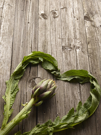 leafed: Close up of artichoke on wooden table LANG_EVOIMAGES