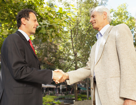 agrees: Businessmen shaking hands outdoors