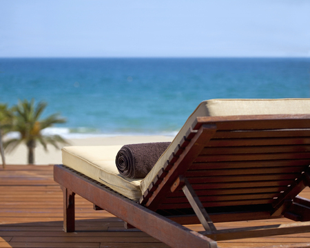 lavishly: Lawn chair on deck at tropical beach LANG_EVOIMAGES
