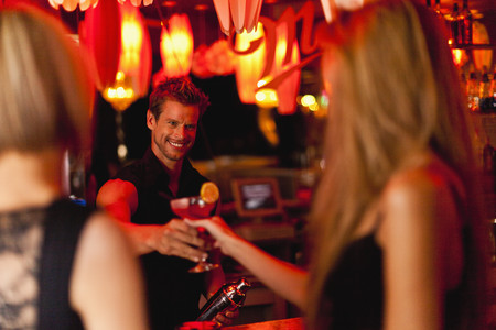Bartender handing woman a cocktail LANG_EVOIMAGES