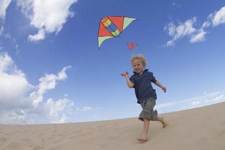 exhilarating: Boy flying kite on sand dune LANG_EVOIMAGES
