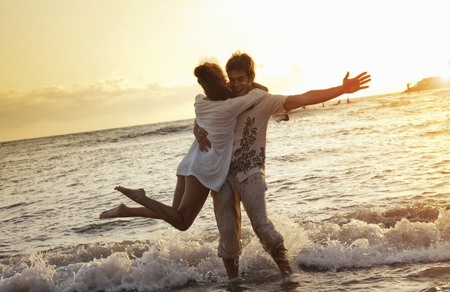 arms lifted up: Couple playing in waves at beach