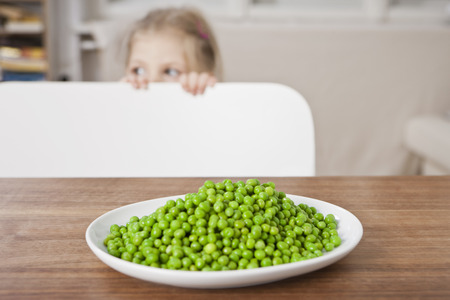 obscuring: Girl hiding from peas at table