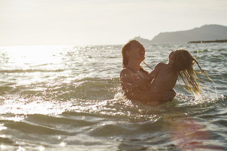 Mother and daughter playing in ocean