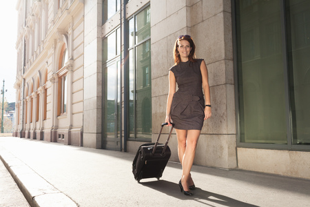 stop and go light: Businesswoman rolling luggage outdoors LANG_EVOIMAGES