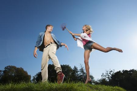 Woman using butterfly net on boyfriend LANG_EVOIMAGES