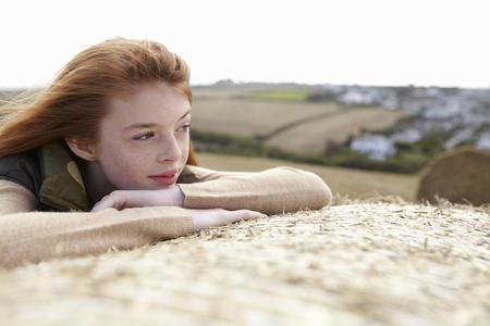 musing: Teenage girl resting on haybale
