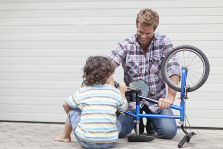 taught man: Father helping son fix bicycle LANG_EVOIMAGES